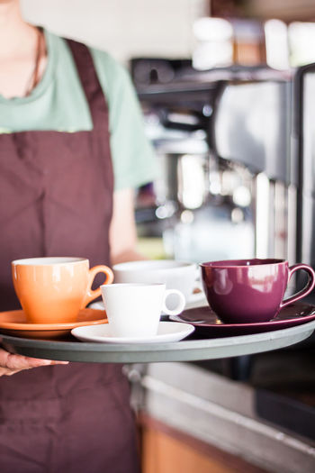 Midsection of waitress holding coffee cups in tray at restaurant