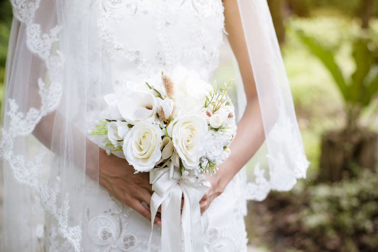 Midsection of woman holding bouquet against white wall