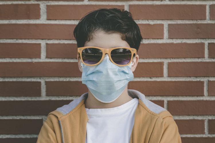 Portrait of man wearing sunglasses against brick wall
