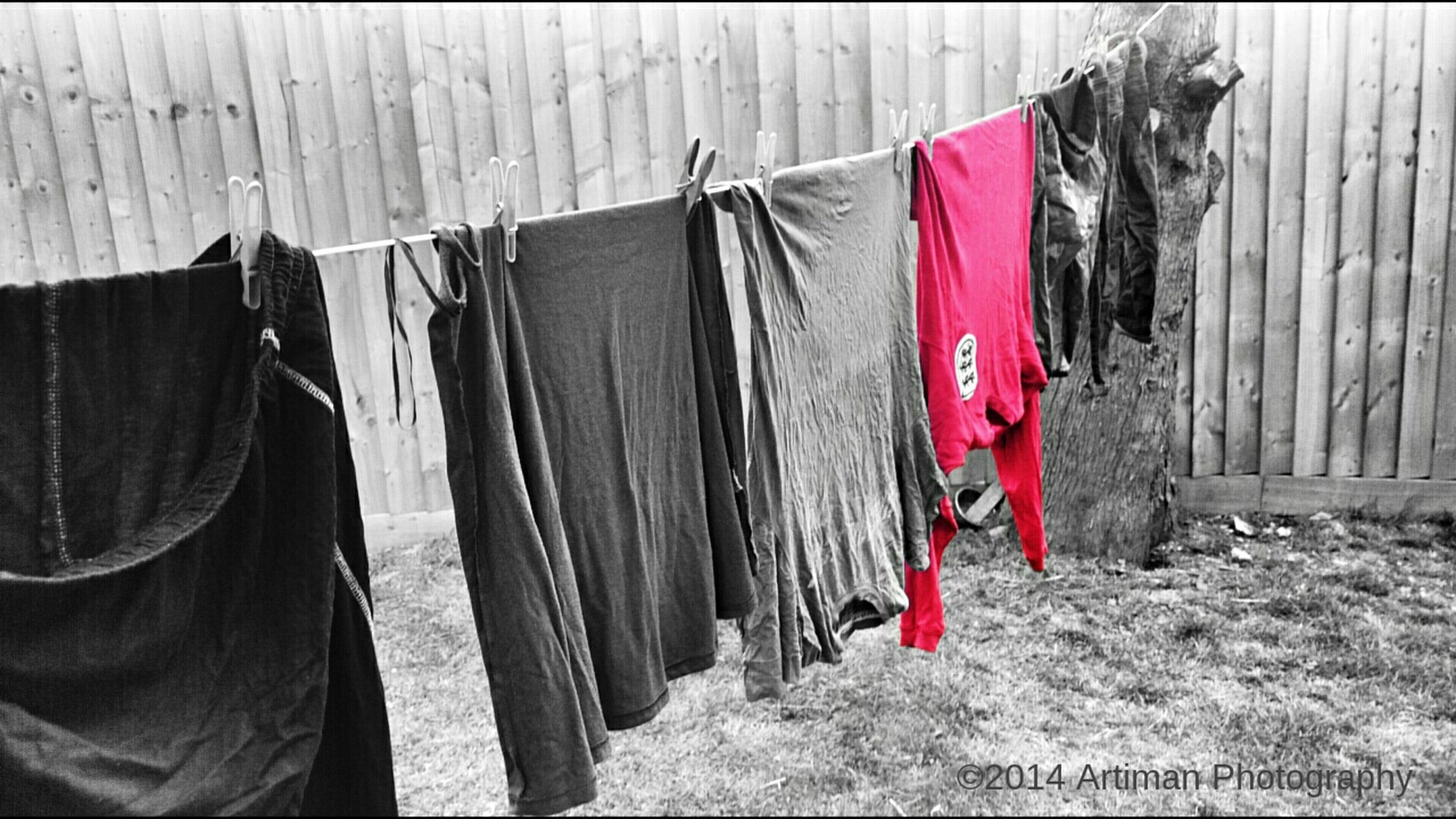 flag, building exterior, architecture, national flag, patriotism, built structure, identity, clothing, men, drying, hanging, graffiti, day, american flag, red, outdoors, protection, clothesline, rear view