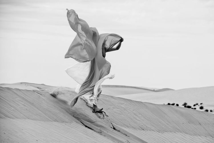 woman and silk meets in a desert BBeautifulDDesertFFreedomSSilhouetteUUtahWWind PowerWWomanaActionbBlack And WhitebBlack And White FridaydDayfFabricfFull LengthNNatureoOne PersonoOutdoorspPassionpPeoplerReal PeoplesSandsSilksSkytTransparentvVacationyYoung Adult