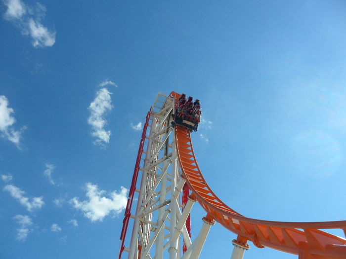 Low Angle View Of Rollercoaster Against Blue Sky