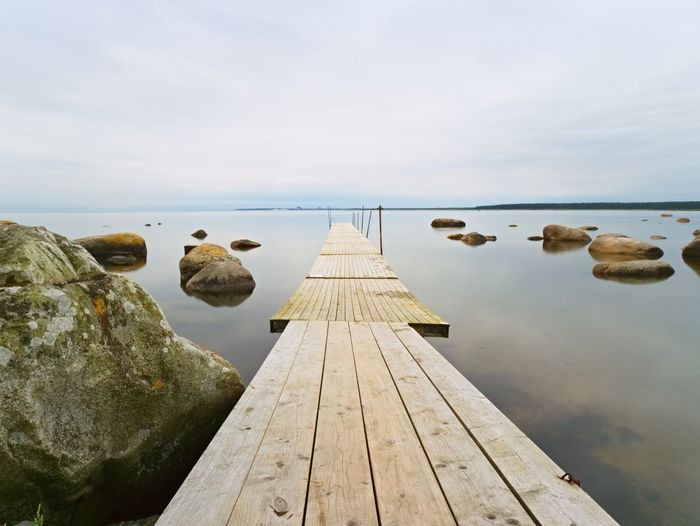 Empty wooden mole in water of lake. old fishing wharf for hired boats and swimmers. long exposure