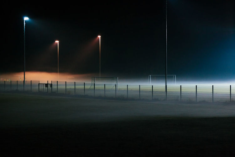 Night Sport Illuminated Sky No People Absence Team Sport Nature Soccer Lighting Equipment Grass Outdoors Fence Barrier Boundary Floodlight Goal Post Dusk Fog Ominous Football Mist Spotlight EyeEmNewHere Colors