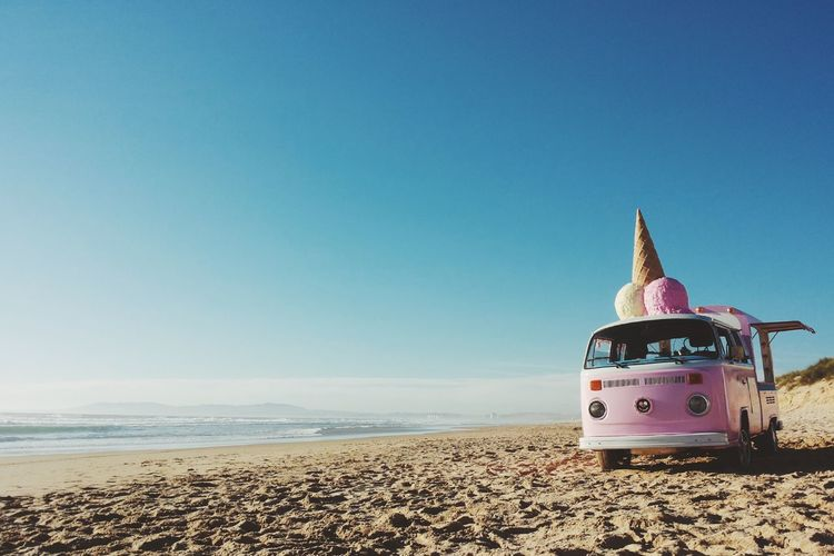 Ice cream van on sandy beach against clear blue sky