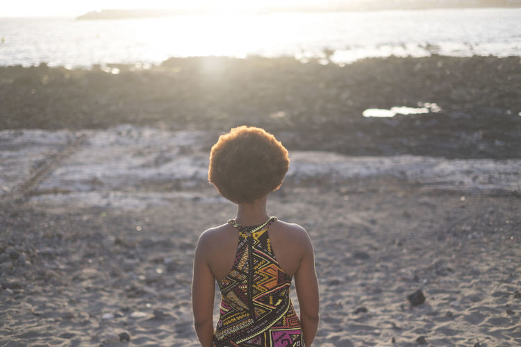 Rear view of woman standing at beach