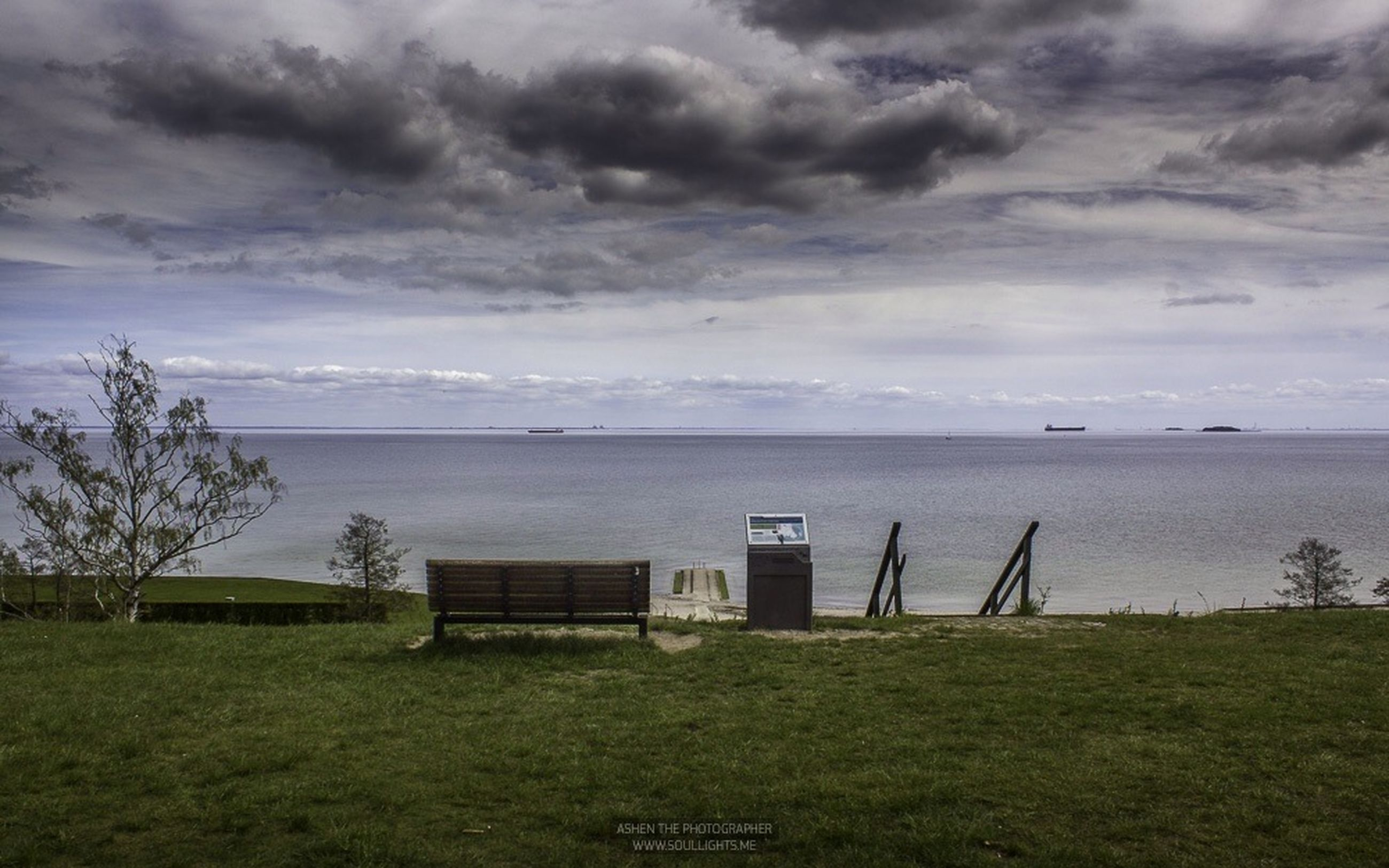 sky, cloud - sky, sea, grass, water, horizon over water, cloudy, tranquil scene, tranquility, scenics, nature, cloud, beauty in nature, field, landscape, weather, idyllic, built structure, day, remote