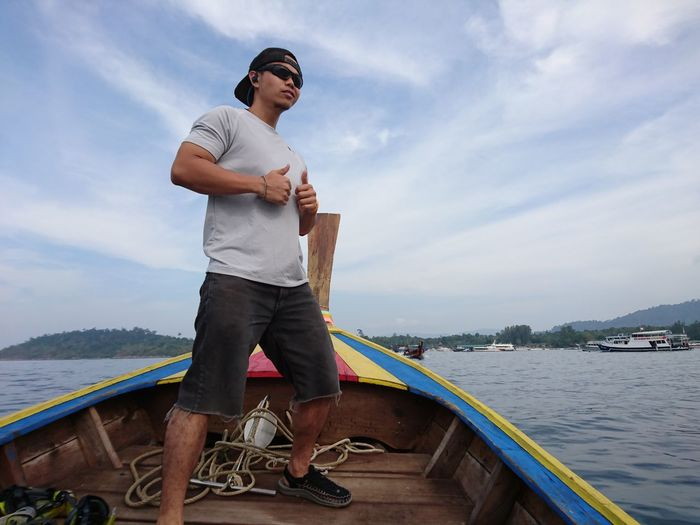 Low angle view of man wearing sunglasses standing in boat on river