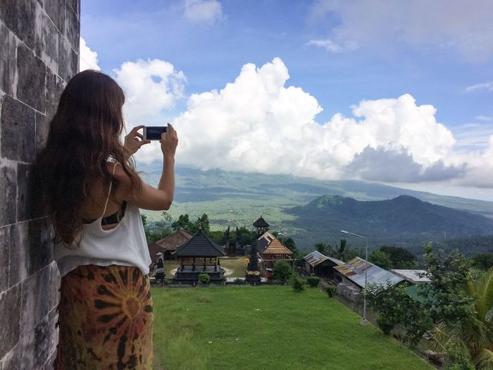 Rear View Of Woman Photographing Of Landscape Against Cloudy Sky With Mobile Phone