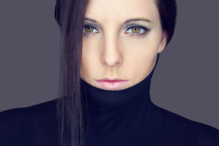Close-Up Portrait Of Young Woman Wearing Turtleneck Against Gray Background