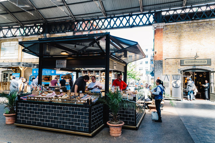Old Spitalfields market with unidentified people. Bakery and pastry stall. The market hosts arts and craft and street food market. Brexit Britain London Uk Antique Architecture Bakery Beautiful British Building Business City Culture Destination England English Europe European  Flea Food Foodie Gastro Handcrafted Interior KINGDOM Landmark Market Marketplace Merchandise Old Pastry People Retail  Retro Revival Shop Shopping Shoreditch Spitalfields Stall Store Street Street Food Tourism Tourist Town Travel Vintage Whitechapel