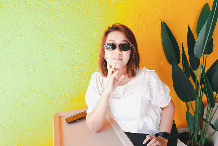 Young woman using phone while sitting on yellow wall