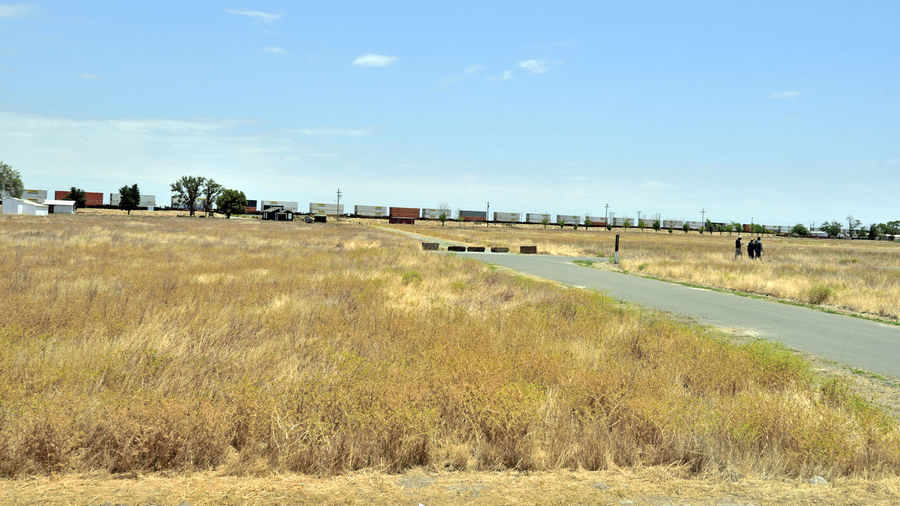Train Passes Thru Allensworth 2 Allenworth, Ca. Lt. Colonel Allen Allensworth Founded Town 1908 BNSF Railway Freight Railroad Train Boxcars Burlington Northern & Santa Fe Railway Merged 1996 Intermodal Freight & Bulk Cargo 2nd Largest Freight Railroad In North America Owned By Berkshire Hathaway Inc Rural Scene Landscape_Collection Landscape_photography Farming Community Grassy Field House Barns Huts Road Train_lovers Train Photography Men Walking