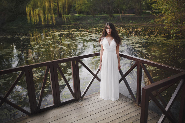 Lovely brooding brunette girl with long hair in white romantic dress stands on a wooden bridge in spring forest or park. The atmosphere of a warm sunny evening. In the background, green trees and wild plants are reflected in the pond. Pond Romantic Beautiful People Beautiful Woman Beauty Beauty In Nature Brooding Day Front View Full Length Leisure Activity Lifestyles Long Hair Looking At Camera Nature One Person Outdoors Portrait Railing Real People Standing Water White Color Women Young Women