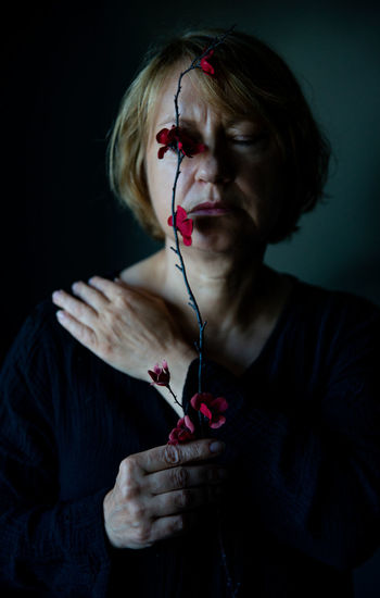 Woman holding red flowers against black background