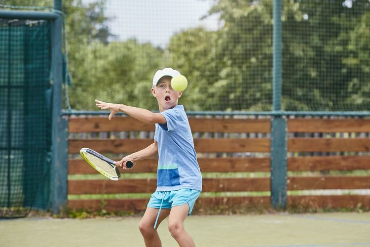 Portrait of cute boy hitting ball with racket at tennis court