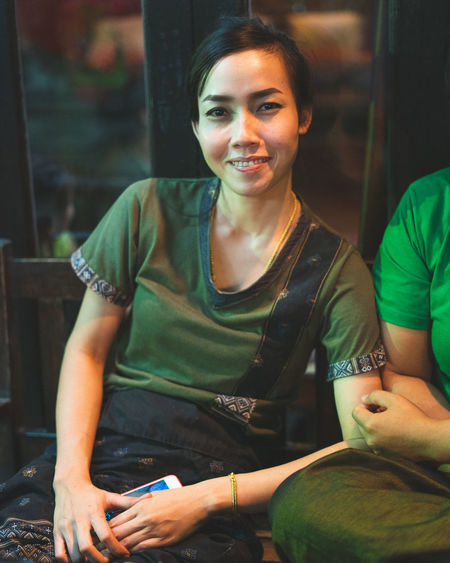Happy people Real People Sitting Looking At Camera Young Adult Portrait Three Quarter Length Smiling Young Women Front View Holding Lifestyles Women Leisure Activity Happiness Hairstyle Masseuse Massage Worker Mobile Phone Green Color Uniform Thailand Thailand_allshots Thailandtravel