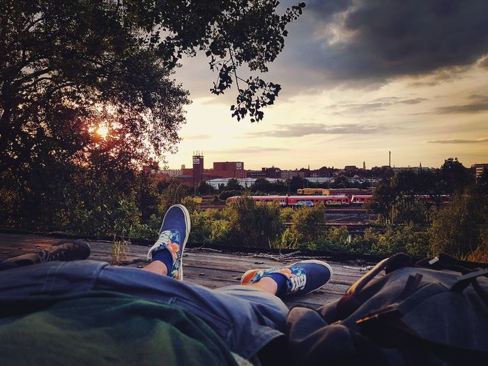 Low section of man relaxing in city against sky during sunset