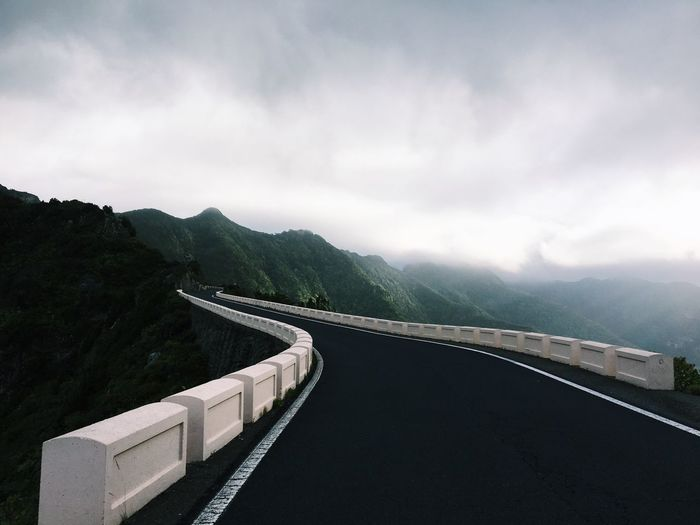 Bridge Amidst Mountains Against Sky During Foggy Weather