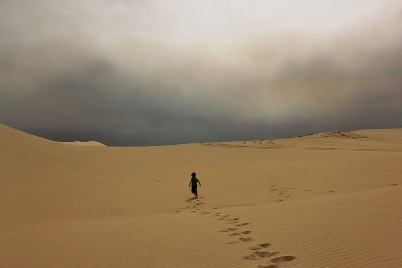 Rear View Of Boy Running On Sand In Desert Against Storm Clouds