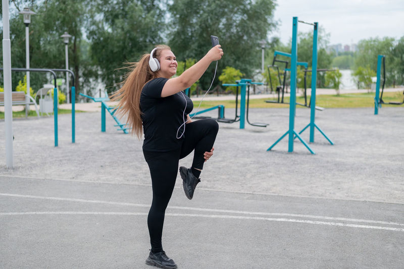 Full length of woman with arms raised in park