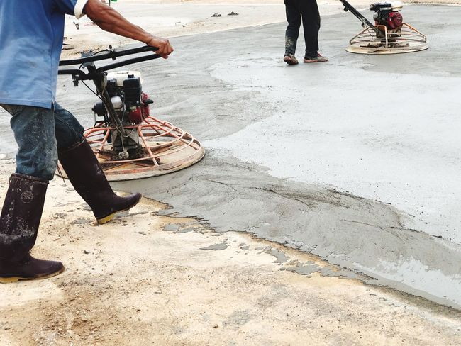 Cement floor grinding surface Scrubbing Worker And Tools Working Day Low Section Real People Men Human Leg Body Part Day Human Body Part Outdoors Human Limb Two People Lifestyles Nature Road Sunlight City Street Working People Transportation Occupation