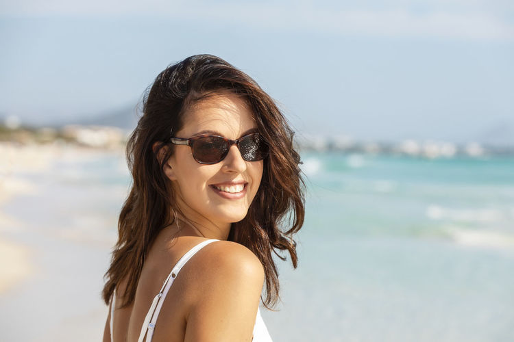 Portrait of smiling young woman at beach