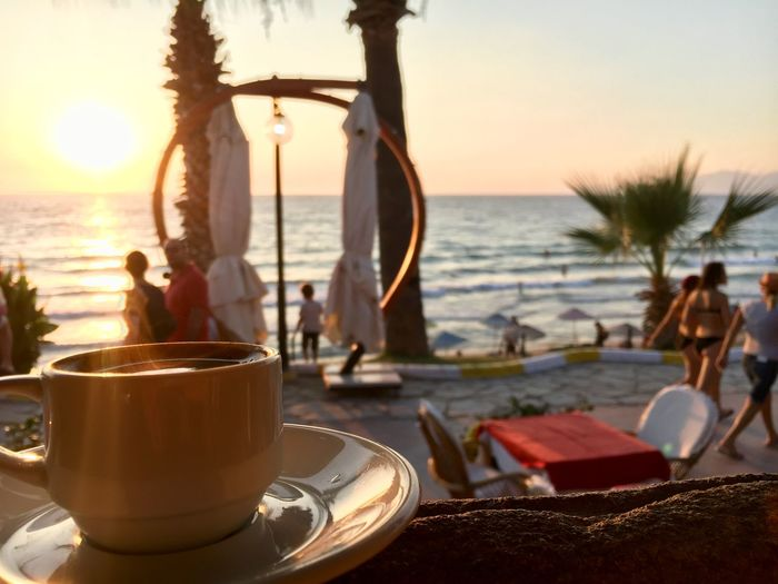 Coffee cup on table by sea against sky during sunset
