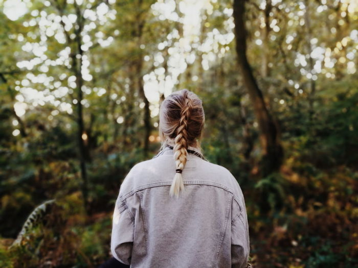 Rear view of woman with braided hair standing against trees at forest