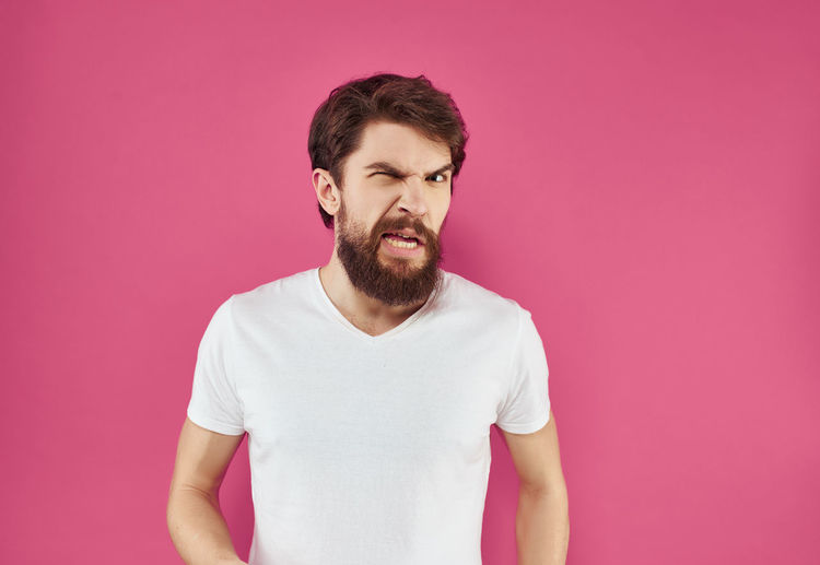 Young man looking away against pink background