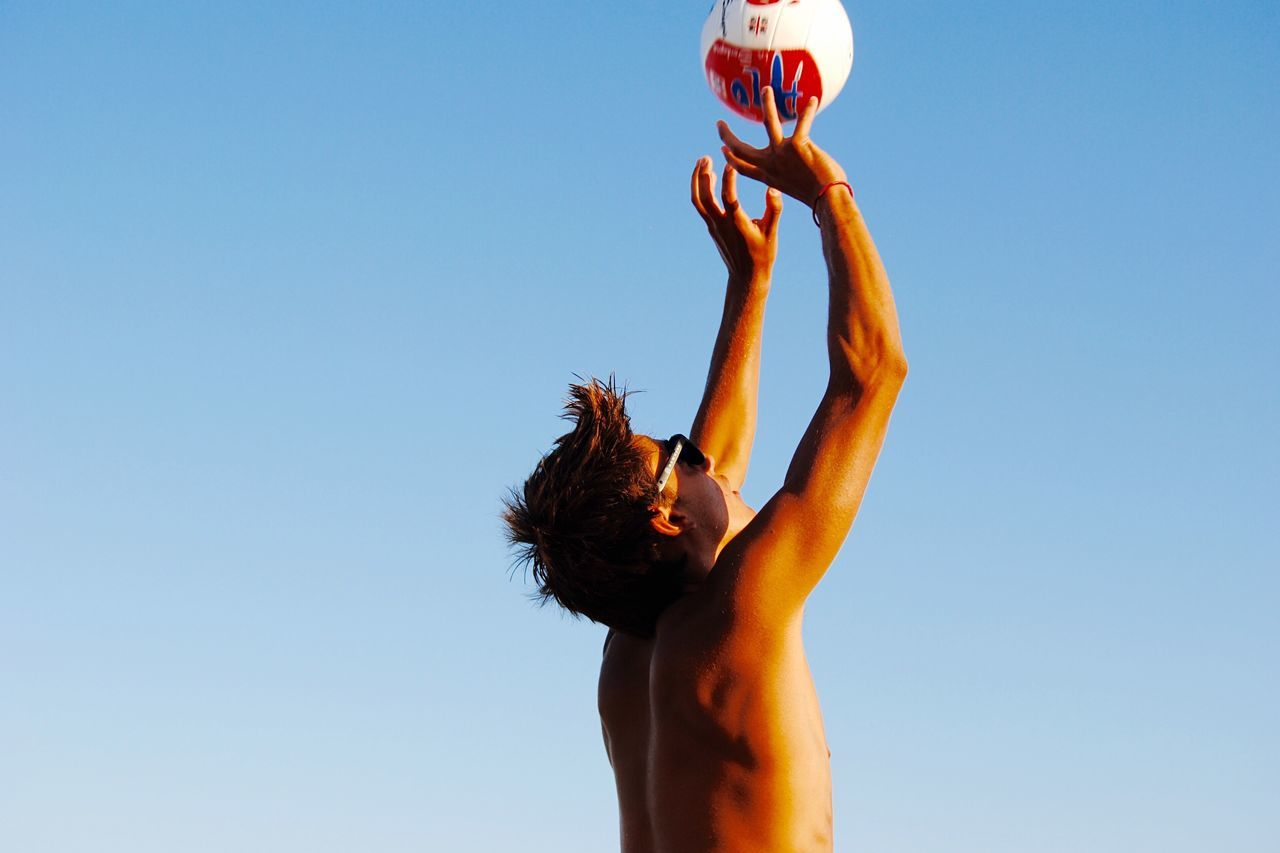 Low angle view of shirtless man playing volleyball against clear blue sky