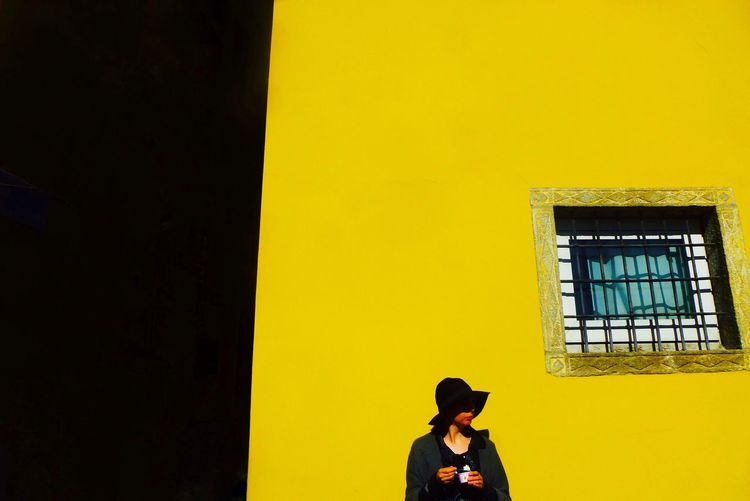 Woman wearing sun hat while standing against yellow building on sunny day