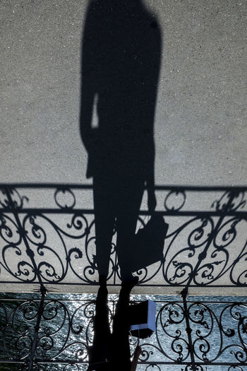 Shadow of person on railing against wall