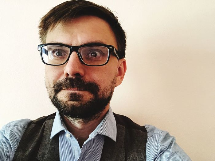 Portrait Of Man Wearing Eyeglasses Against Wall