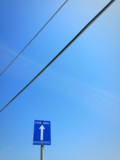 Low Angle View Of One Way Sign Against Blue Sky