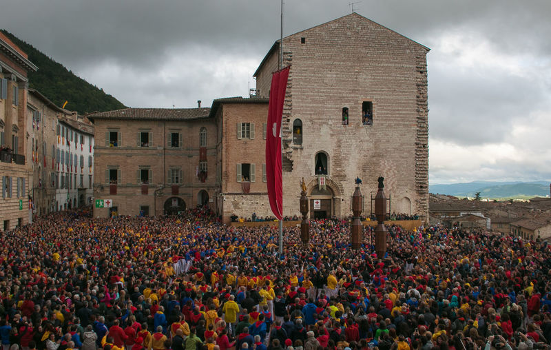 The famous festa dei ceri with many people in the historic center of Gubbio medieval village, Umbria Feast Gubbio, Perugia, Italy Travel Architecture Building Building Exterior Celebration Cloud - Sky Corsa Dei Ceri Crowd Europe Festa Dei Ceri Group Of People Gubbio High Angle View Italy Large Group Of People Manifestation Multi Colored Piazza Grande Real People Sky Spectator Tourism Umbria