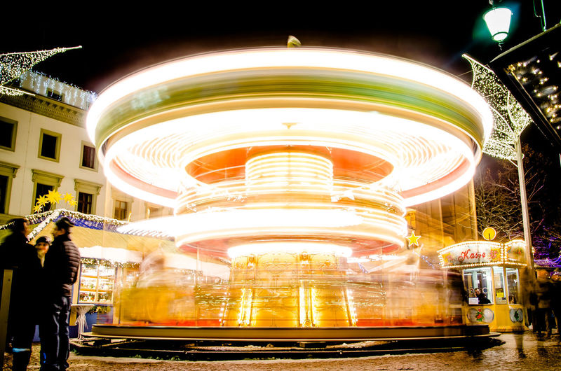 Blurred motion of illuminated carousel at night