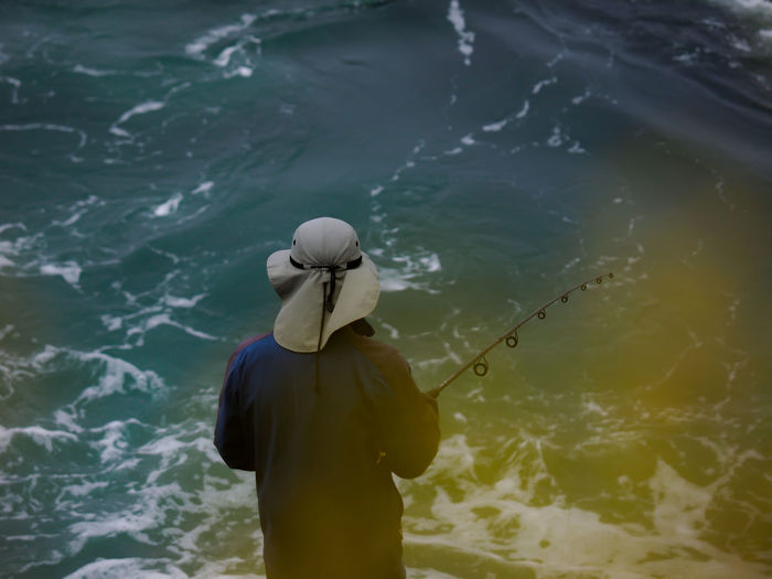 High angle rear view of man fishing in sea