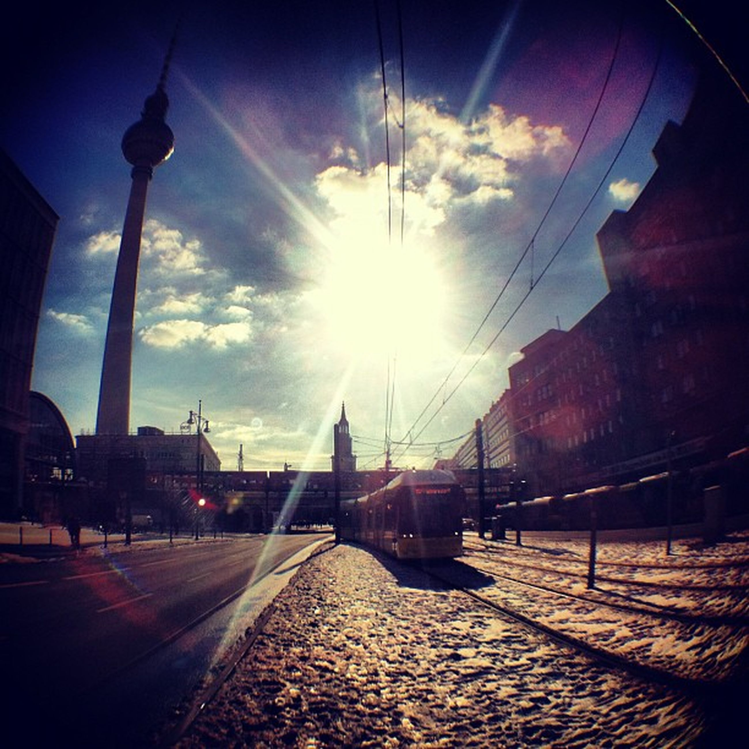 sun, architecture, built structure, building exterior, sunbeam, sunlight, sky, lens flare, the way forward, city, transportation, street light, diminishing perspective, connection, vanishing point, cloud - sky, street, sunny, road, sunset