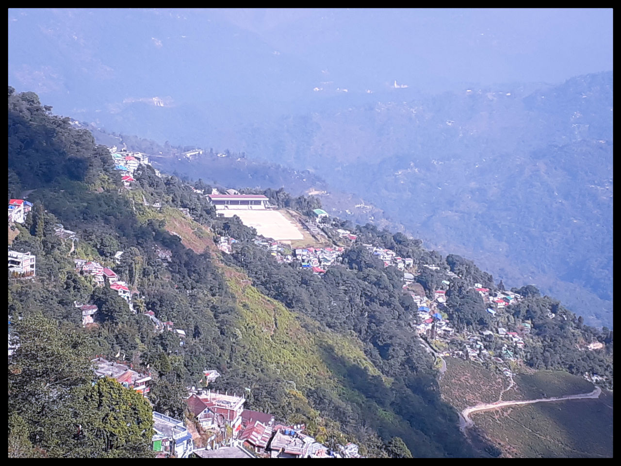 HIGH ANGLE VIEW OF TOWNSCAPE BY MOUNTAIN