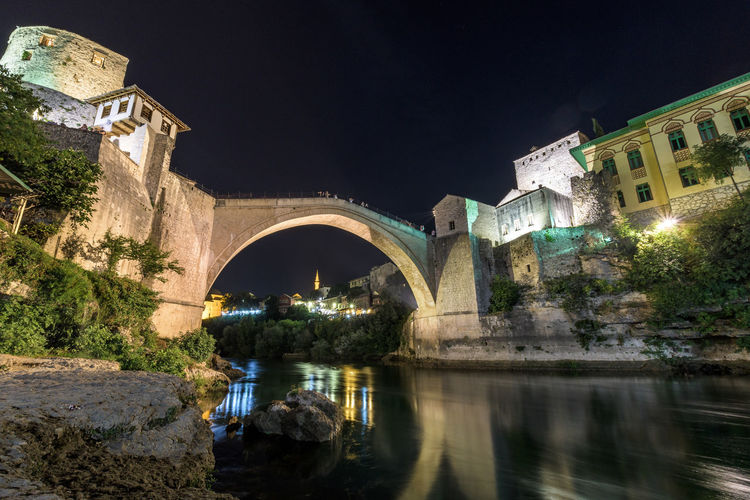 Arch bridge over river amidst illuminated buildings against clear sky at night