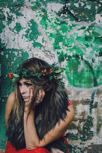 Model Wearing Wreath Against Weathered Wall