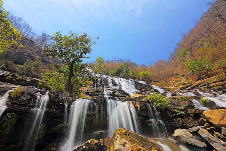 Beautiful view of Mae Ya Waterfall on hot sun day in the summer, northern of Thailand Beauty In Nature Tree Scenics - Nature Water Waterfall Plant Forest Rock Flowing Water Nature Motion Rock - Object Non-urban Scene Long Exposure Solid Land Environment No People Tranquil Scene Flowing Outdoors Power In Nature Falling Water Rainforest Doi Inthanon Chiangmai Thailand Mae Ya Waterfall Amazing Autumn Beautiful Cascade Landscape Yellow Wonderful