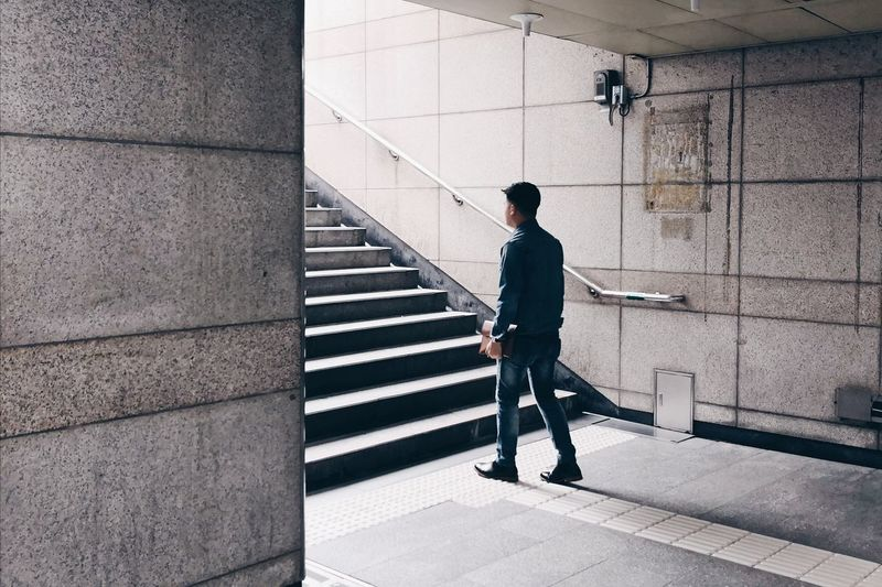 Rear view of man walking on staircase of building