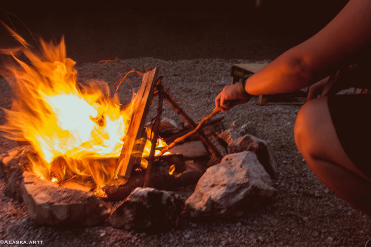 Cropped image of person preparing fire on wood