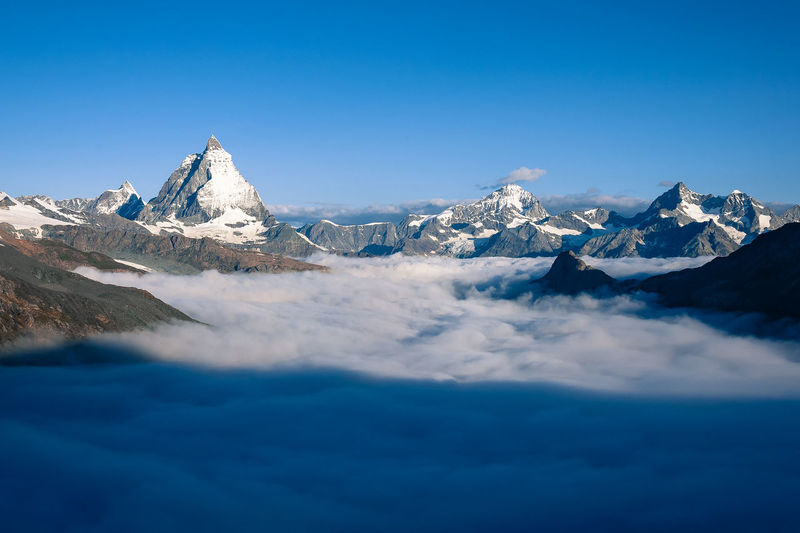 a cloud sea in front of the Matterhorn Alpine Alpine Hiking Alpine Landscape The Great Outdoors - 2017 EyeEm Awards Blue Sky Cloud - Sky Cold Temperature Day EyeEmNewHere Glacier Hiking Idyllic Landscape Mountain Mountain Range Nature No People Outdoors Scenics Sky Snow Snowcapped Mountain Tranquil Scene Tranquility