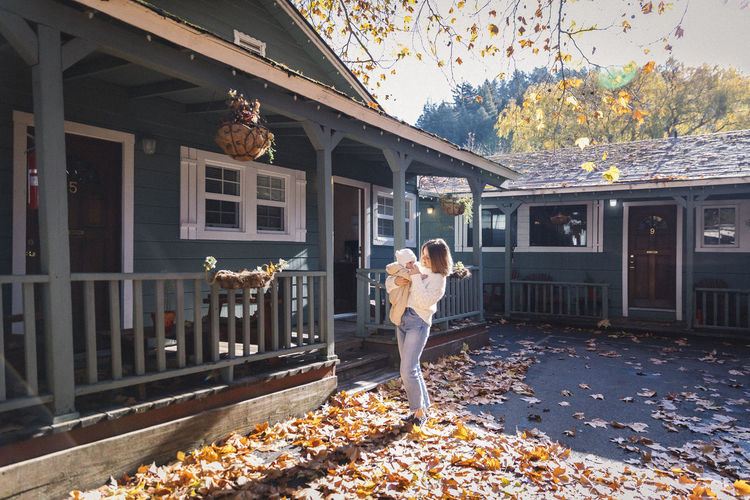 Woman standing by leaves on building during autumn