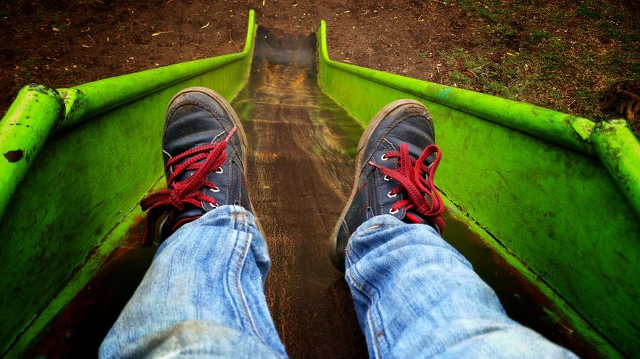 Low Section Of Man Sliding On Slide At Playground