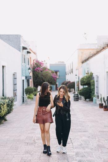 Two women  walking in city against sky