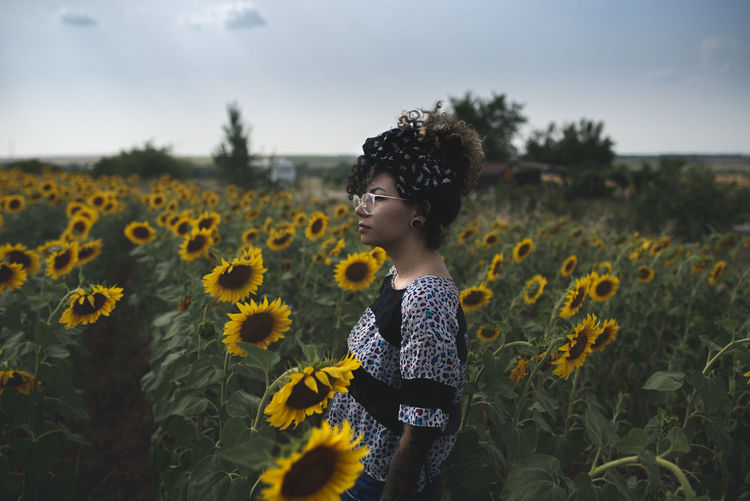 Side view of woman standing amidst sunflowers on field against sky